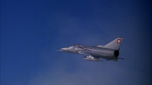 tracking shot of jet saab viggen 37e fighter plane model. pov behind jet. jet explodes. model used for visual effect. see nosecone hanging by string at end. see blue sky, light clouds in background. explosions. - visual effect stock videos & royalty-free footage