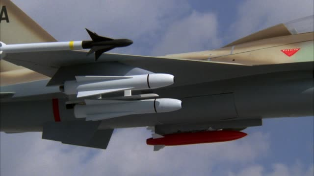 stockvideo's en b-roll-footage met close angle of military f-16 fighter jet wing with missiles. missile shoots off wing of jet. - raket wapen