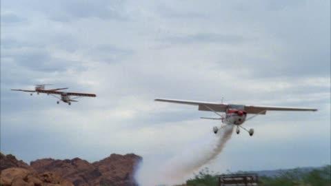 tracking shot of three propeller powered stunt airplanes flying in formation over desert landscape. middle east. - propeller bildbanksvideor och videomaterial från bakom kulisserna