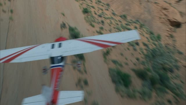 tracking shot of red and white propeller powered stunt airplane flying through desert canyon. plane executes a series of maneuvers very close to cliff faces. middle east. - propeller bildbanksvideor och videomaterial från bakom kulisserna