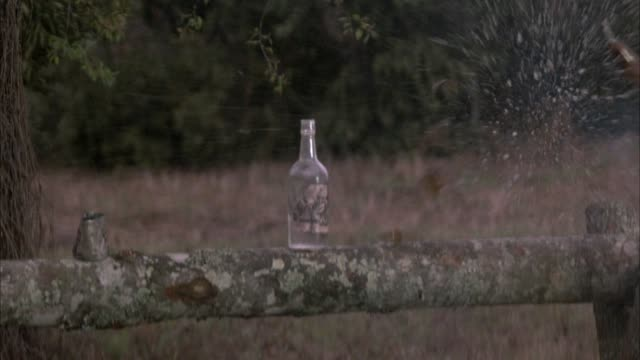 vídeos y material grabado en eventos de stock de medium angle of two glass bottles standing on a wood fence post. bottle on right explodes then bottle on left, probably from gunshot. explosions. - botella