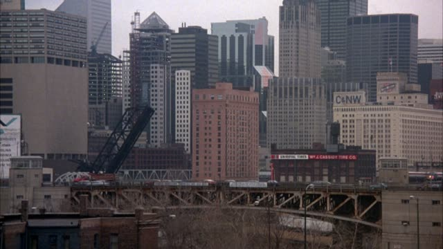pan left to right of bridge with downtown area visible in background. police car with lights on enters screen from left and moves across screen to right. camera pans to follow car over bridge but stops and car exits screen to left. elevated train in backg - toronto stock videos & royalty-free footage