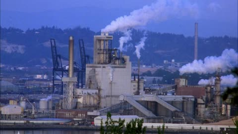 medium angle of factory or plant, steam or smoke coming out of smokestacks. mountains visible in background. - pierce county washington state stock videos & royalty-free footage