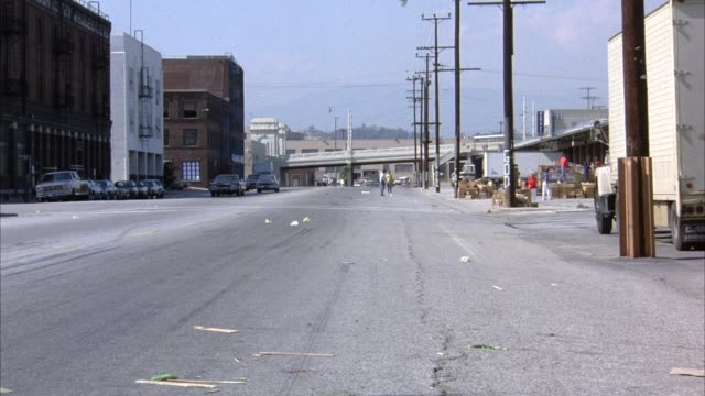 """medium straight back angle of street in commercial area. red truck appears from front right, turns right onto street. black cadillac on red truck's passenger side. cars collide next to each other as they turn into alley on right. rear of truck reads """"guar - armored truck stock videos and b-roll footage"""