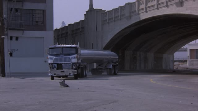 medium angle of downtown area. concrete overpass visible on the right, warehouse building on the left. armored car enters from the left and stops in foreground. fuel tanker truck enters from right and pulls behind armored car. truck ignites into explosion - armored truck stock videos and b-roll footage
