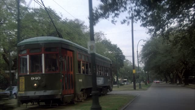 3/4 front process plate driver's side of new orleans streetcar in center of road in residential area. street signs, traffic signals, trees, electrical wires on sides of road. two and three story houses on right side of road. - new orleans stock videos & royalty-free footage