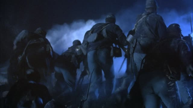 medium angle of union soldiers in civil war. soldiers stand up and charge forward toward fort from sand hill. wide angle of charging soldiers toward smoke and mine explosions ahead. soldiers carry muskets or rifles, see american flag among soldiers. explo - bürgerkrieg stock-videos und b-roll-filmmaterial