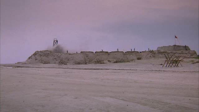 medium angle of fort on beach. pans left, confederate flag on right end of fort, explosion or smoke on left end. dozen of confederate soldiers on top of fort. wood barricade in front of fort on sand. explosions. - confederate states army stock-videos und b-roll-filmmaterial