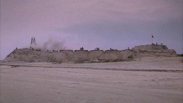 medium angle of fort on beach. pans left, confederate flag on right end of fort, explosion or smoke on left end, soldiers run away from smoke. dozen of confederate soldiers on top of fort. wood barricades in front of fort on sand. explosions. - confederate states of america stock videos & royalty-free footage