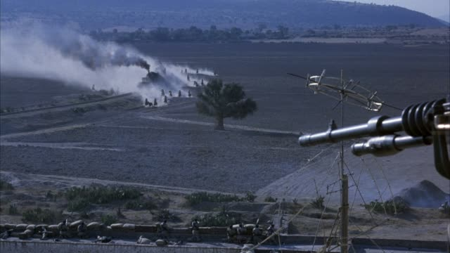 high angle down of steam engine train approaching left in desert. men on horses ride on both sides of train. machine gun in foreground. large dust cloud around train. - machine gun stock videos and b-roll footage