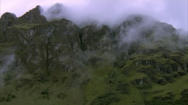 MEDIUM ANGLE OF ROCK OUTCROPPING, MOUNTAIN PEAK OR SUMMIT WITH VEGETATION. SOME FOG DRIFTS ACROSS TOP OF FRAME TO RIGHT.