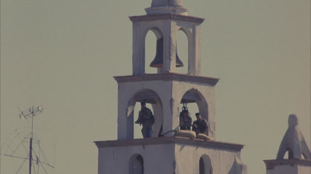 medium angle of soldiers stationed or posted on top of bell tower in battle. see soldiers shooting rifle and machine gun. soldiers are wearing khaki uniforms. action. - machine gun stock videos and b-roll footage