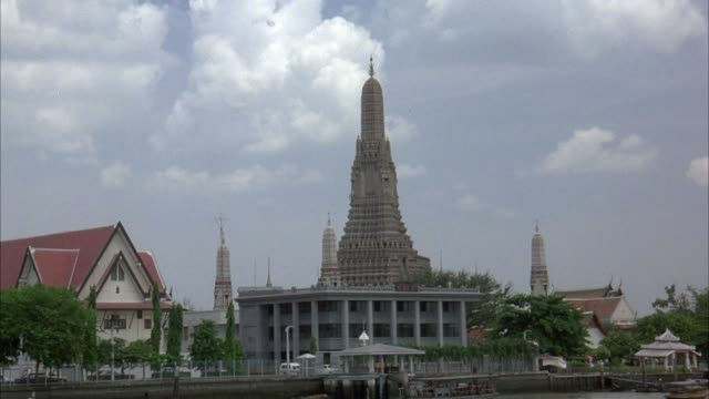 wide angle moving pov of wat arun temple in bangkok, thailand. white office building on left side. temple has four small spires and one large spire. see clouds in background. see large mansions in background. pov could be from boat or car. - bangkok stock-videos und b-roll-filmmaterial