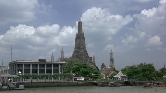 process plate of wat arun temple in bangkok, thailand. white office building on left side. temple has four small spires and one large spire. see clouds in background. see large mansions in background. pov could be from boat or car. - bangkok stock-videos und b-roll-filmmaterial