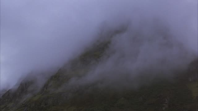 UP ANGLE OF PEAK OF MOUNTAIN. FOG BLOWS AROUND MOUNTAIN AND DOMINATES BACKGROUND.