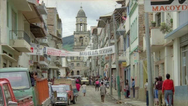 medium angle of downtown area in city. see dirt road and people walking along street. see church steeple in background. see yellow taxi drive towards camera. could be marketplace. - ecuador stock videos & royalty-free footage