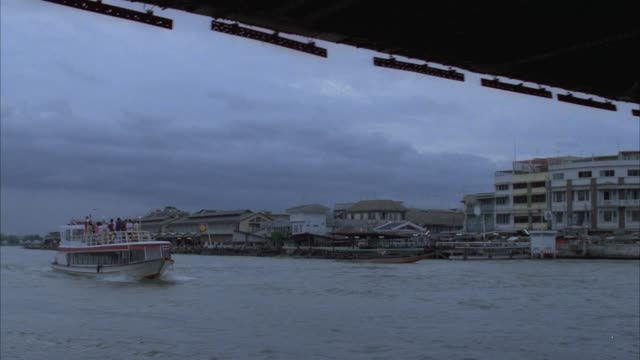 tracking shot of ferry boat driving on the chao phraya river. boat drives under bridge. see residences, industrial areas in background. see wat arun temple in far background. - bangkok stock-videos und b-roll-filmmaterial