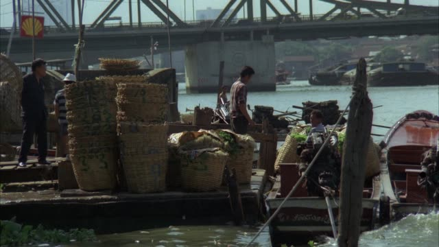 medium angle of dock establishing chao phraya river. see bridge, see boats parked on dock and men working on dock. see baskets piled on dock and goods for trade. - bangkok stock-videos und b-roll-filmmaterial