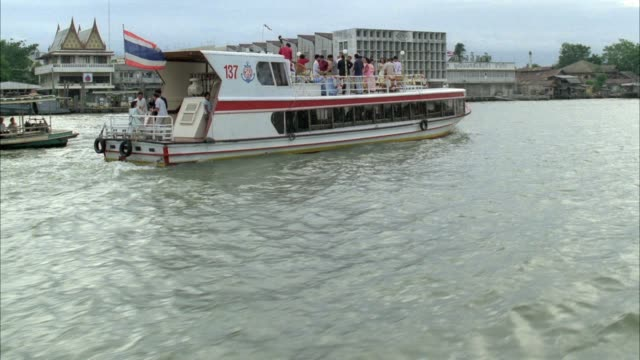 medium angle of ferry boat driving on the chao phraya river. see urban area in background. see people having cocktail party or celebration on top of ferry. could be used for tour boat. - ausflugsboot stock-videos und b-roll-filmmaterial