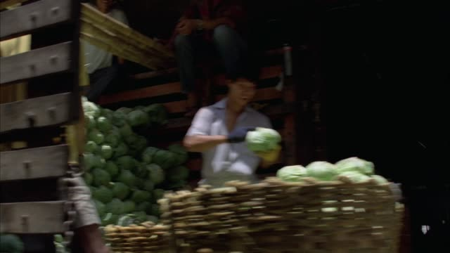 medium angle walking pov through south east asian marketplace. see workers on back of trucks piling produce into large baskets. see small open produce stands on left. - bangkok stock-videos und b-roll-filmmaterial
