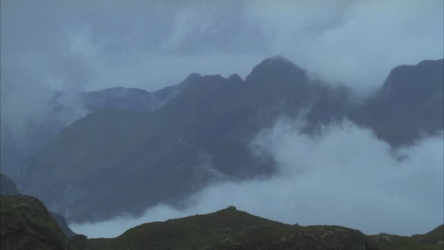wide angle of hills or mountains. see clouds or fog. could be andes mountains. - ecuador stock-videos und b-roll-filmmaterial