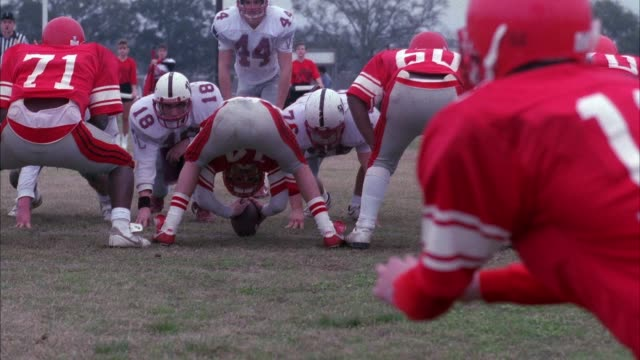medium angle of high school football game. teams are red and white. white team has letters vc on helmet. see red team snap ball to place holder. placeholder then sets ball for kick. kick is good, red team celebrates. see referee. - football goal post stock videos and b-roll footage