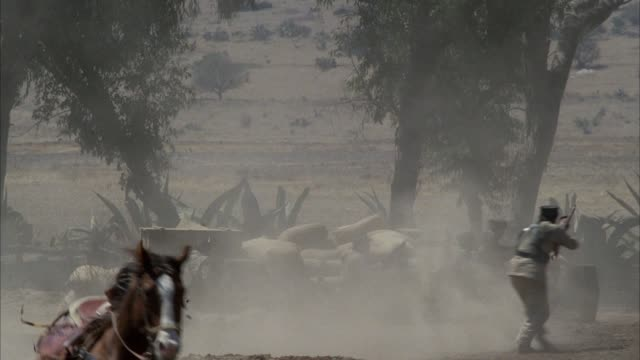 MEDIUM ANGLE OF MILITARY CAMP DURING BATTLE. SEE SOLDIERS ON HORSEBACK AND TRAIN COME INTO SHOT, FIRING AT TROOPS IN CAMP. CAMERA PANS RIGHT TO LEFT TO FOLLOW TRAIN. TRAIN STOPS AND SOLDIERS JUMP OFF TRAIN WHILE FIRING GUNS. SOLDIERS STORM THE CAMP. MARIA