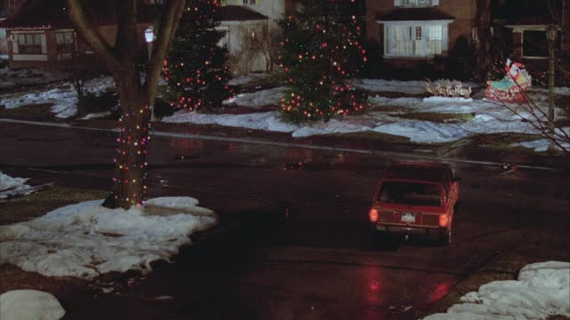 medium angle of red jeep cherokee driving in residential area during christmas season. see snow on ground, christmas lights and decorations. - public celebratory event stock videos & royalty-free footage