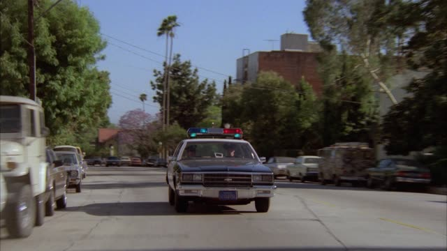 tracking shot of police car engaged in car chase. see sirens and bizbar flashing. drives through residential area. - 1986 stock-videos und b-roll-filmmaterial