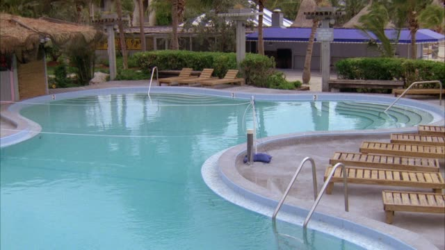 medium angle of resort or spa pool. see deck or beach chairs, palm trees, water. see wind blowing. see volleyball net across pool. - volleyball net stock videos & royalty-free footage