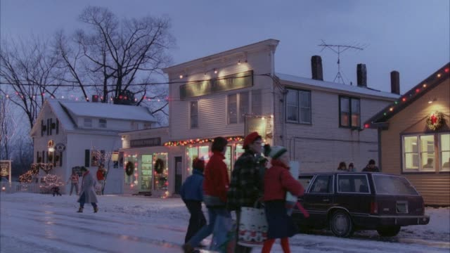 medium angle establishing small town during christmas. see christmas lights, store, snow. - town stock videos & royalty-free footage