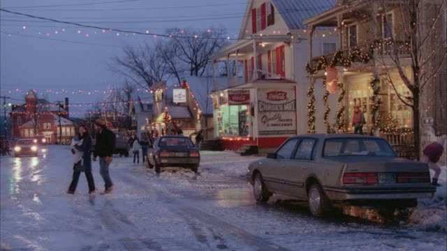 medium angle establishing small town during christmas. see christmas lights, store, snow. see blue dodge dakota drive up and park in front of restaurant, hotel, or church. - vermont stock videos & royalty-free footage