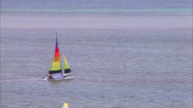 medium angle of catamaran boat with rainbow sail sailing across ocean. - 双胴船点の映像素材/bロール