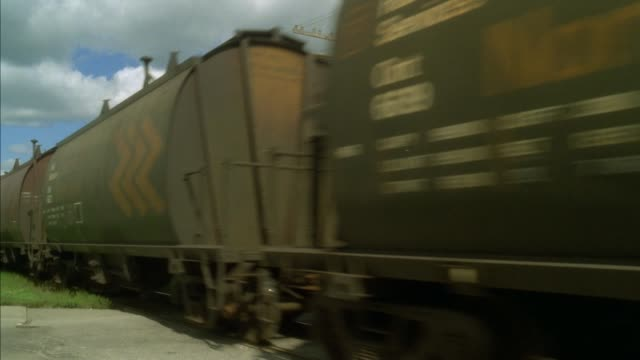 """medium angle of lumber yard or sawmill with white letters that say """"northern planing mills co. ltd."""" see very long freight train pass by on train tracks. train has three locomotives and caboose, cars say """"cn"""" on them. neg cut. - cargo train stock videos & royalty-free footage"""