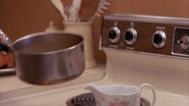 close angle of pouring gravy from pot into gravy boat or small pitcher in kitchen. - vermont stock videos & royalty-free footage
