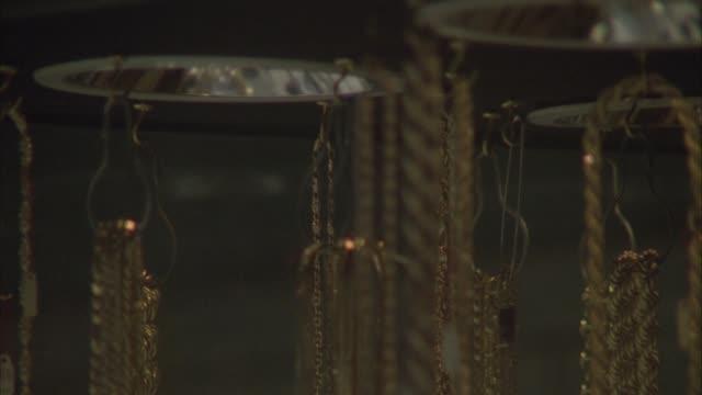 vídeos y material grabado en eventos de stock de close angle of jewelry store window. see gold and silver necklaces on display. see pedestrians walk in front of window. neg cut. - 1980 1989