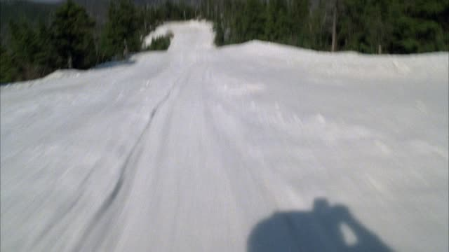 medium angle moving pov, sliding down ski hill. see valley and mountain in background.  see evergreen trees. see snow flying onto camera lens. skiing down hill. - ski slope stock videos & royalty-free footage