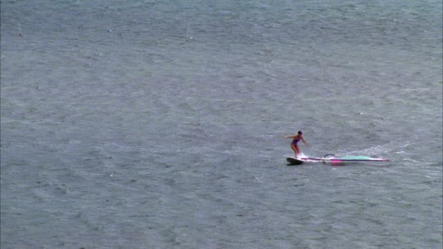 medium angle shot of woman, female windsurfer windsurfing on calm body of water dropping sail and falling off of board. she attempts to climb back onto board. - windsurf video stock e b–roll