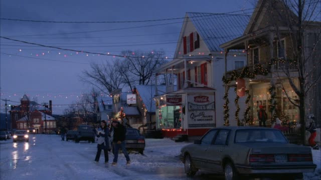 medium angle of blue mid 80's pickup truck with small camper shell over pickup bed pulling up and parking on a snow covered street. appears to be a church or hotel in background. see christmas lights. see pickup door open slightly then close. see sedan pa - town stock videos & royalty-free footage
