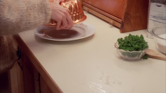close angle of jell-o mold on counter in kitchen. see hands in shot turning out mold onto plate. parsley is added on top of jell-o. see food, cooking. - vermont stock videos & royalty-free footage