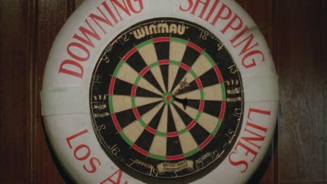 """medium angle of dartboard. surrounding white border with red writing reads """"downtown shipping lines los angeles"""". see dart on bull's eye. see two more darts land in inner ring. - ダーツ点の映像素材/bロール"""