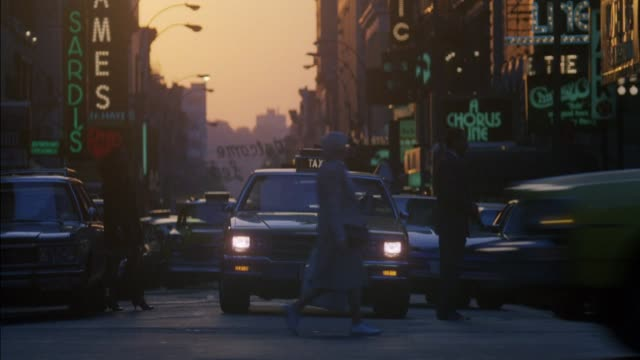 """vídeos y material grabado en eventos de stock de medium angle of downtown los angeles street with signs for broadway shows. see cars, trucks and pedestrians passing in front. see """"a chorus line"""" sign. off screen signal changes and waiting cars and taxis now approach or turn right. - 1980 1989"""
