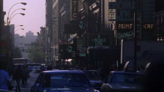 "stockvideo's en b-roll-footage met up angle of downtown broadway area with high rise office buildings. see signs for ""shubert theatre"", ""broadhurst"" and partially blocked ""majestic"". pan down to street with passing cars and pedestrians. pans up and down several times. - 1980 1989"