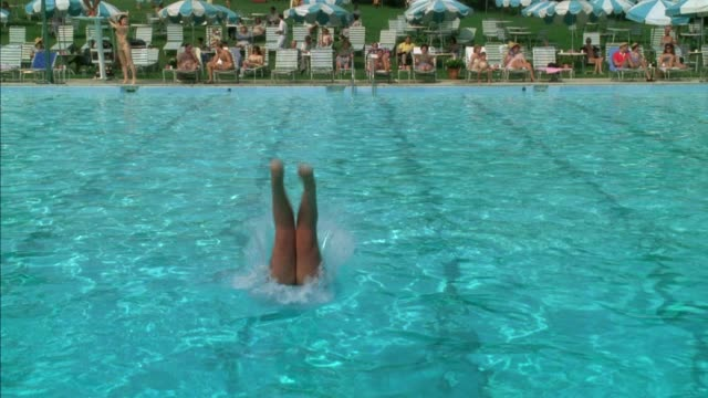 wide angle of pool with people lounging and lying in pool chairs. see large colonial style house with lawn in background. woman in bikini bathing suit talking to lifeguard in tower at right. old woman with swim cap dives from top into view and swim away t - country club stock videos & royalty-free footage