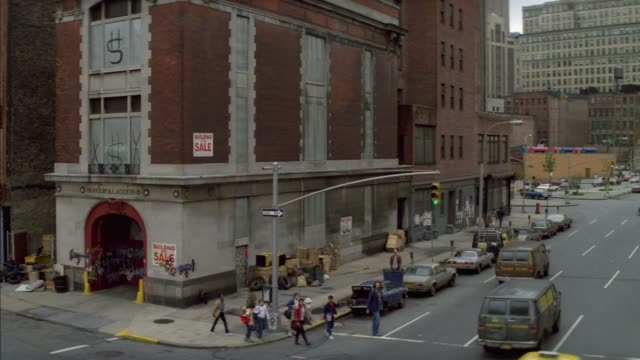 """wide angle of downtown street corner. see fire station with """"sale"""" sign on it. see cars parked on left side of street and other cars driving on one-way street to right. see pedestrians start to cross street. - one way stock videos & royalty-free footage"""