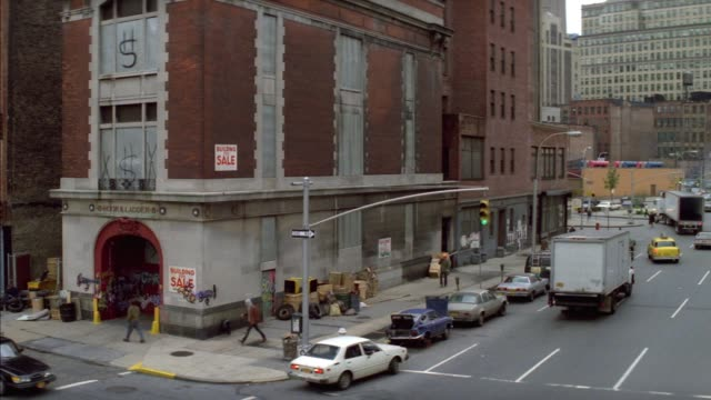 """wide angle of downtown street corner. see fire station with """"sale"""" sign on it. see cars parked on left side of street and other cars driving on one-way street to right. see white car back around corner. - one way stock videos & royalty-free footage"""