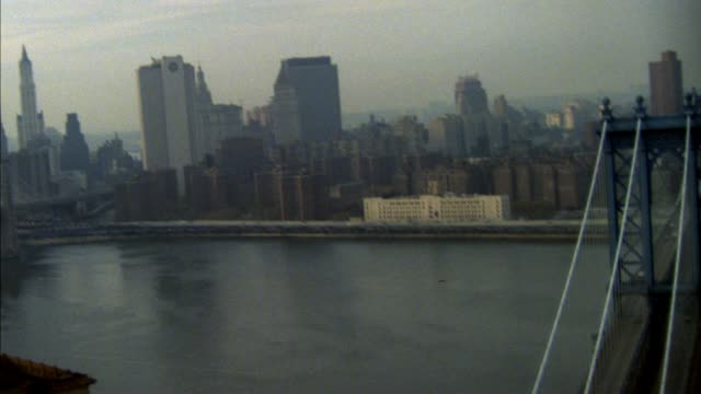 aerial over manhattan bridge, pans left to new york city skyline, lower manhattan. brooklyn bridge, east river.  world trade center, twin towers.new york city skyline. overcast, hazy sky. - manhattan bridge stock videos and b-roll footage