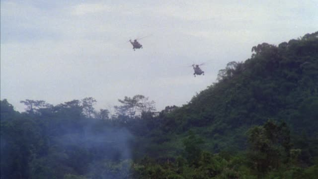 TRACKING SHOT OF TWO MILITARY HELICOPTERS FLYING OVER JUNGLE. SEE SMOKE RISING IN FOREGROUND. FOLLOWS HELICOPTERS AS THEY FLY FORWARD THEN EXIT RIGHT.