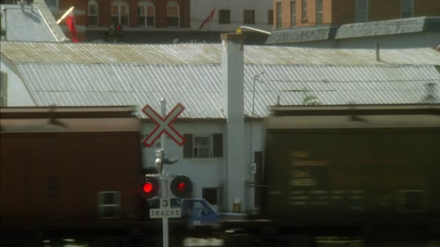 pullback from flashing lights at railroad crossing to small town. see freight train moving right to left, brick buildings in background. pans quickly left to lumber yard surrounded by trees. - cargo train stock videos & royalty-free footage