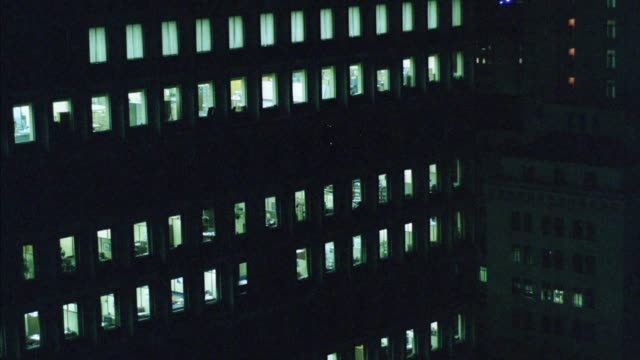 aerial of los angeles, pass by several high rise office buildings and offices, see inside. flashing lights from helicopter reflect in office building. man opens curtains to look at pov, continues flying. - 1986 stock-videos und b-roll-filmmaterial